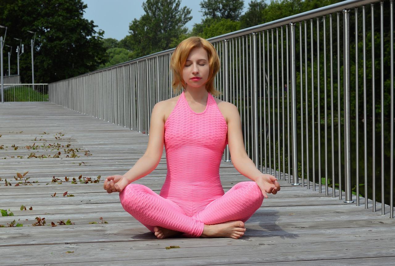 Frau in pinkem Anzug macht Yoga.