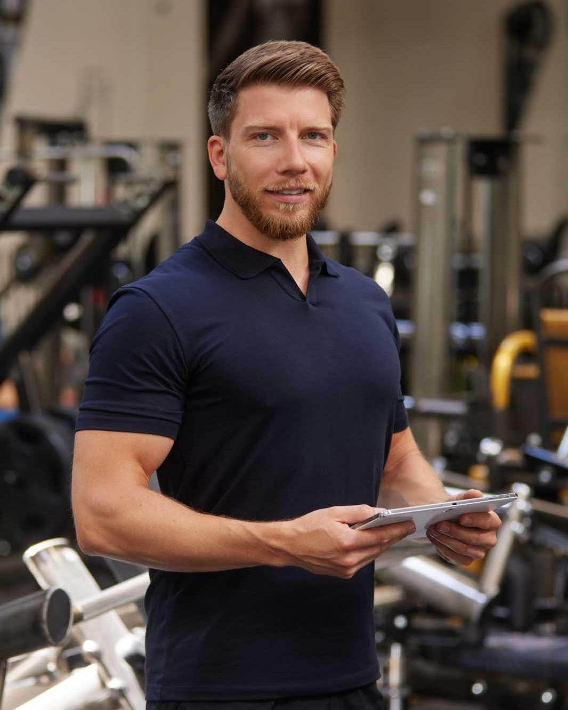 Martin Fiedler Persoanl Trainer und Sportwissenschaftler steht mittem im Gym. Er trägt ein dunkelblaues Polohemd und hält ein Tablet in den Händen.
