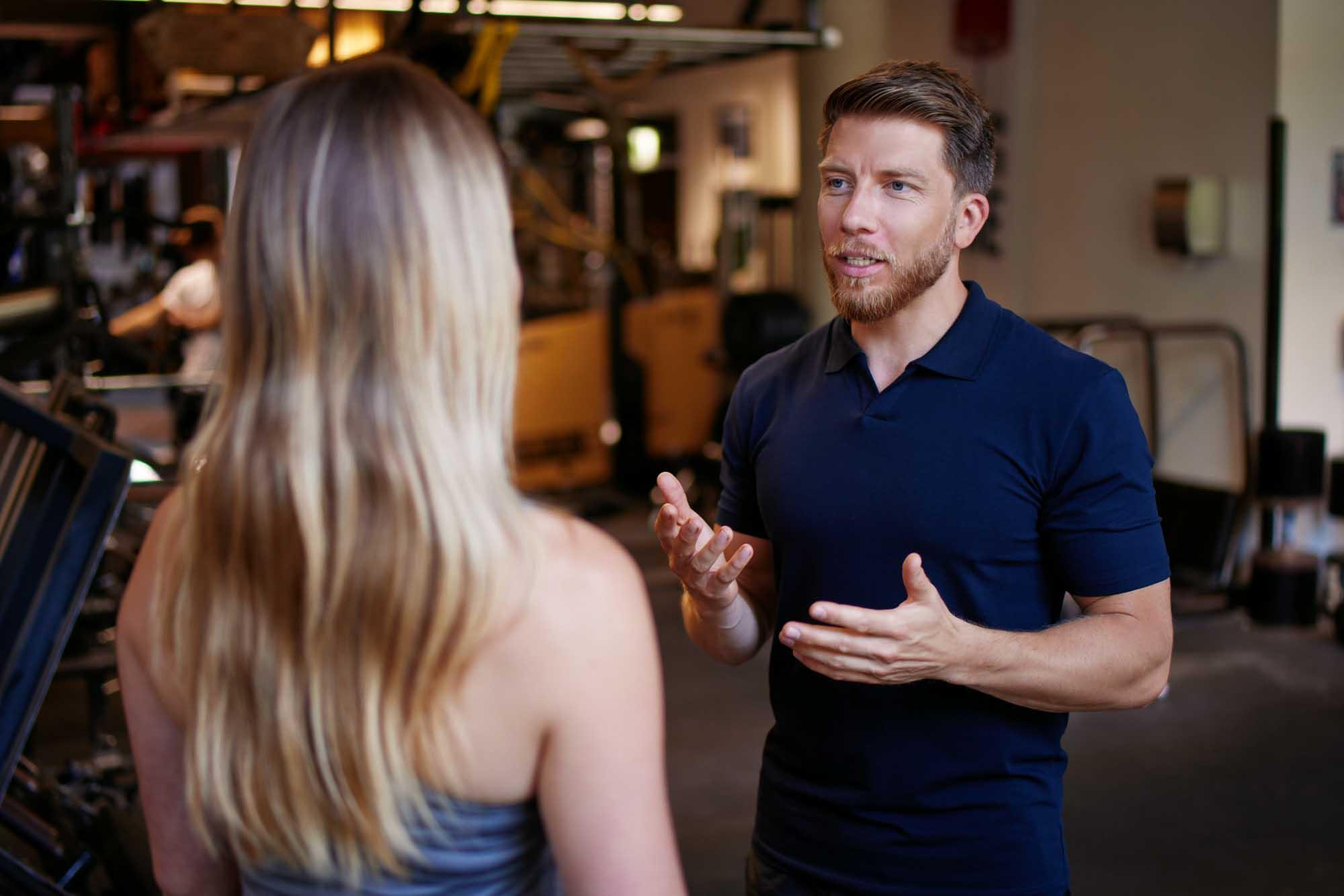 Personal Trainer und Sportwissenschaftler Martin Fiedler steht im Fitnessstudio einer Klientin gegenüber und berät sie.