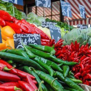 Auf diesem Bild ist ein Gemüsestand auf einem Markt zu sehen.